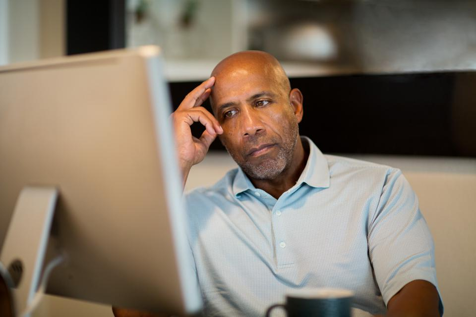 Mature African American man looking frustrated.