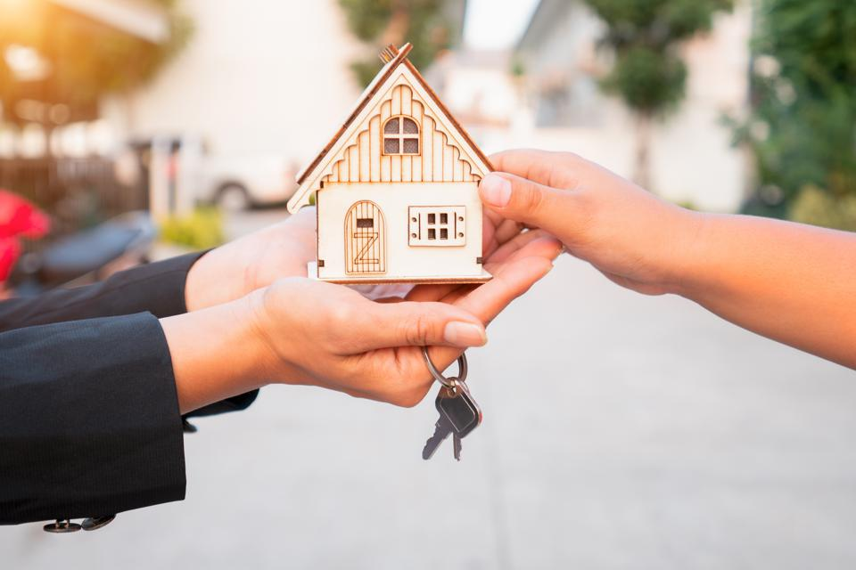 Salesman carrying a model house in hand is delivering the house key to the buyer,Customers receive home keys from home sales sales,Deliver house keys between seller and buyer.Home sales concept home and relocation and sun light.