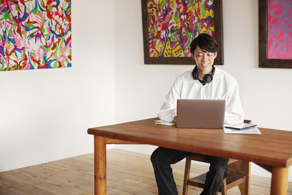 Japanese man siting at a table in an art gallery, looking at laptop computer.