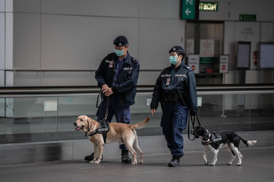 Police agents wear surgical masks at Hong Kong International...