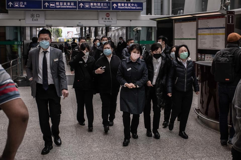 Airport staff wear surgical masks at the arrival terminal at...