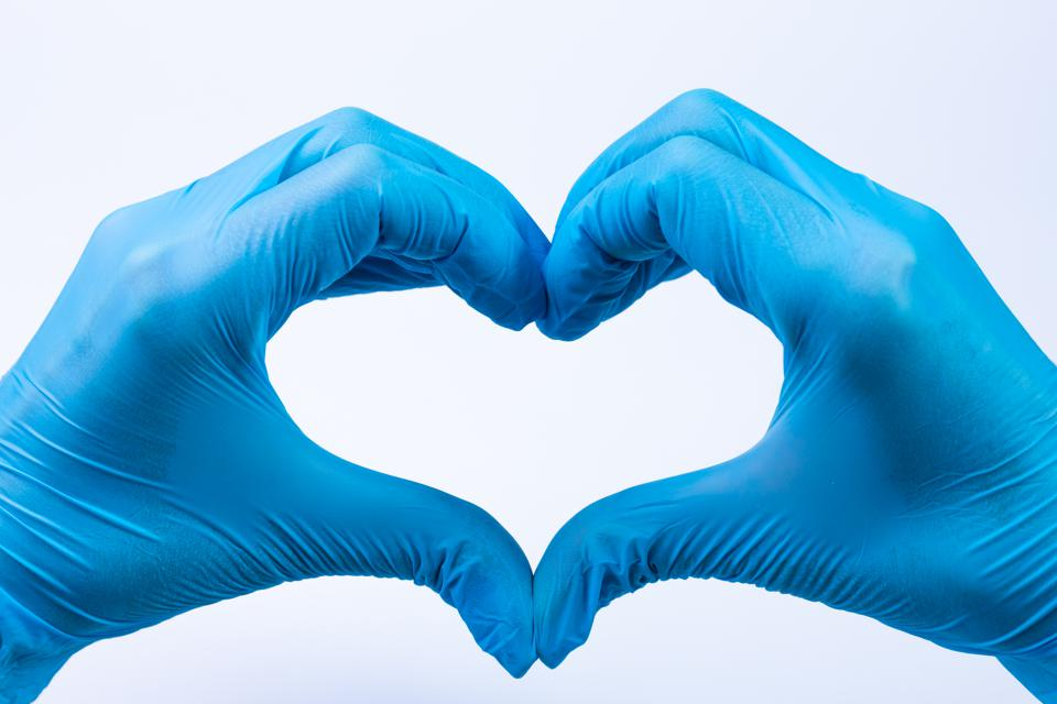 Doctor's hands making heart shape isolated on white