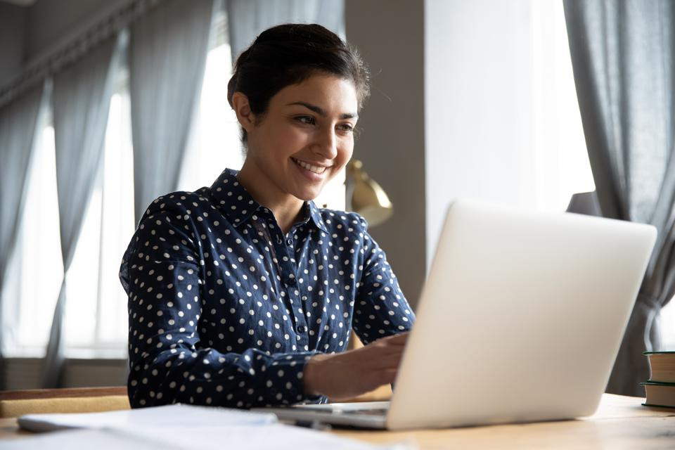 Smiling professional typing on laptop at table