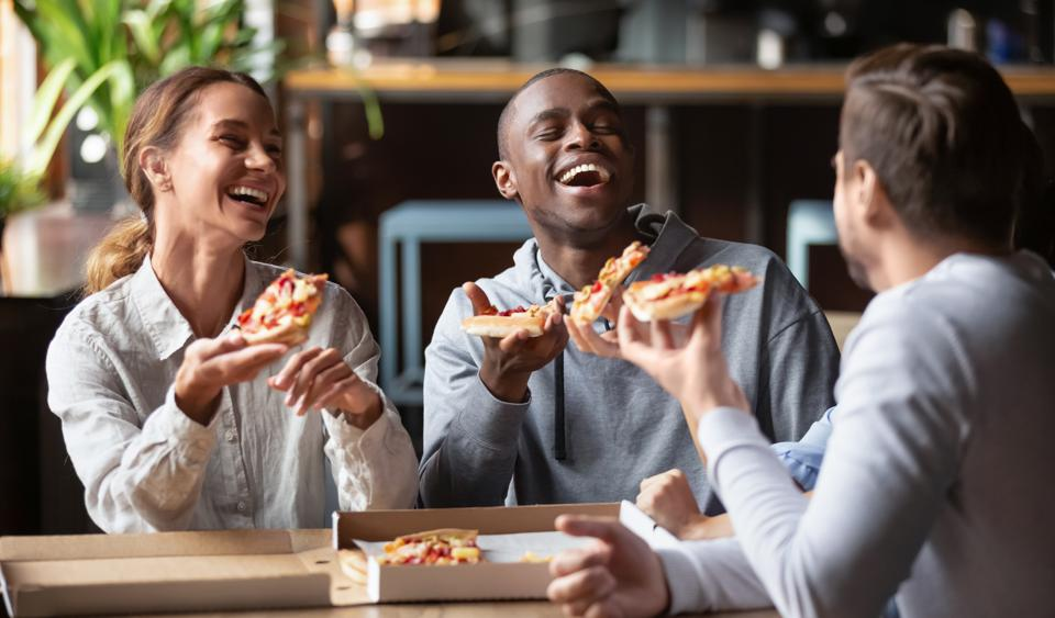 Joyful multicultural friends laughing sharing takeaway pizza meal together