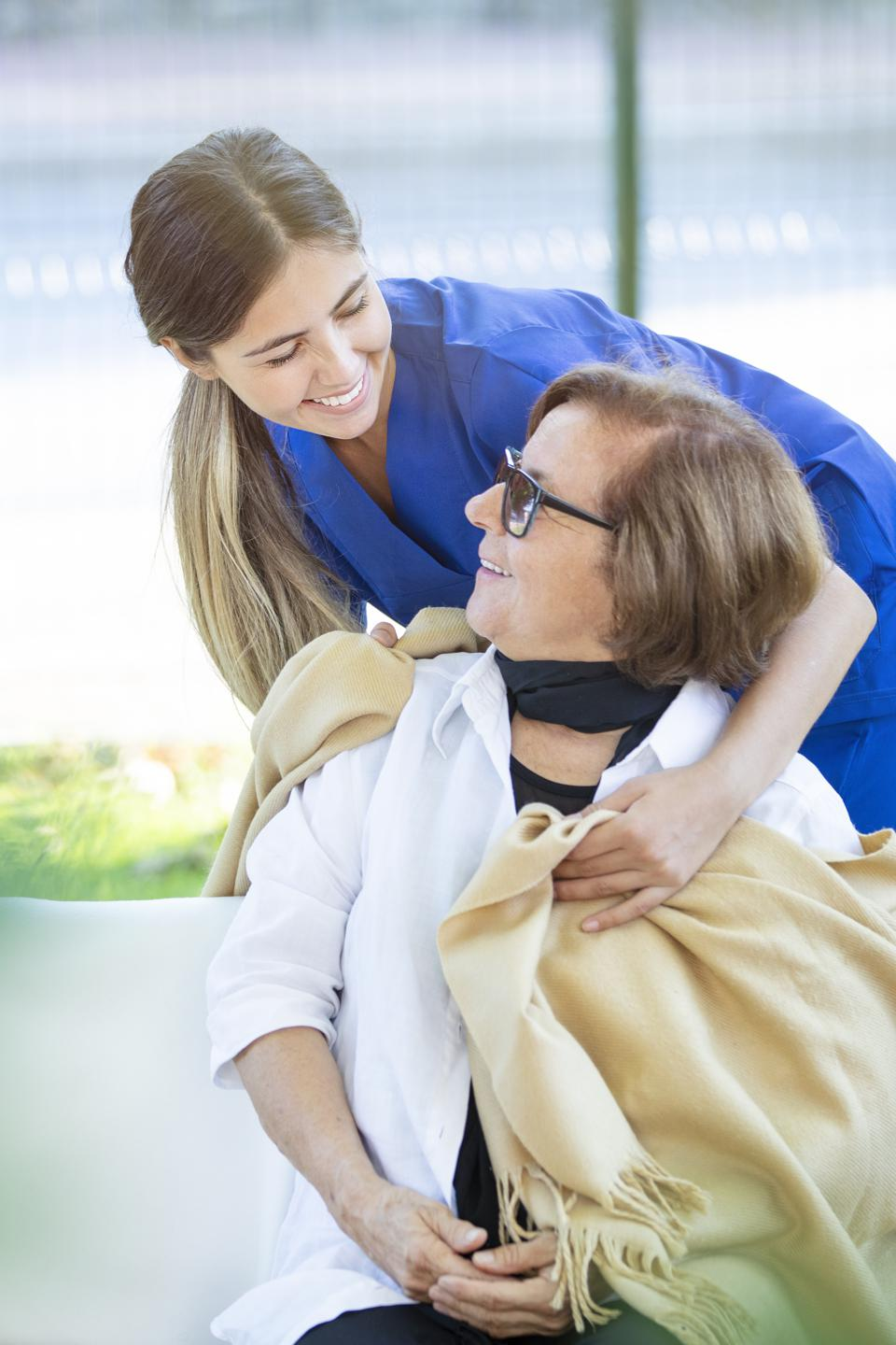 Nurse helping old woman for comfort and care