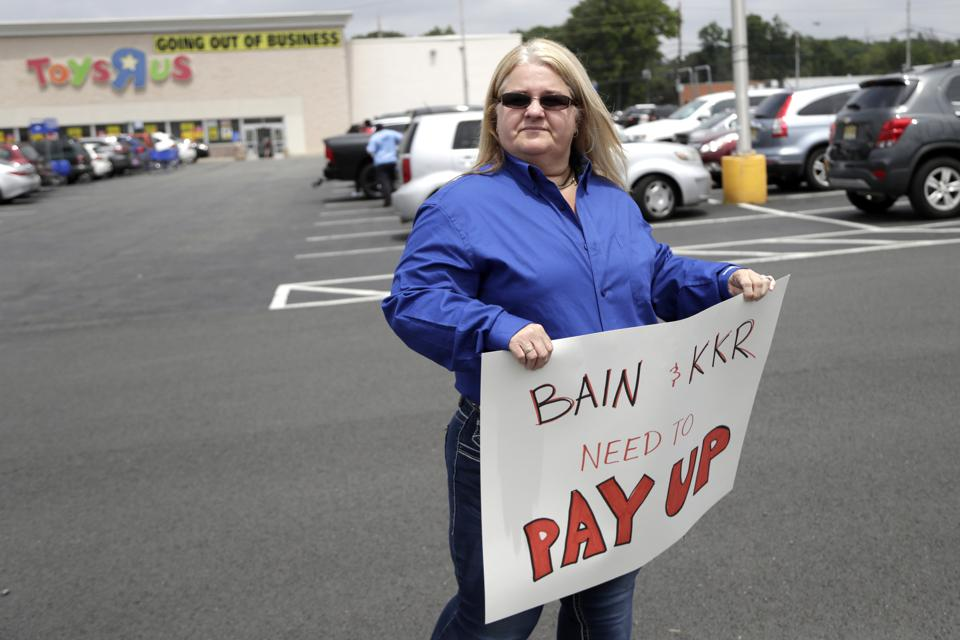 A photo of Toys R Us employee Cheryl Claude, holding a sign asking for severance pay at a rally in Totowa, N.J.