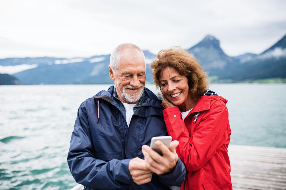 Cheerful senior couple tourist standing by lake in nature on holiday, using smartphone.