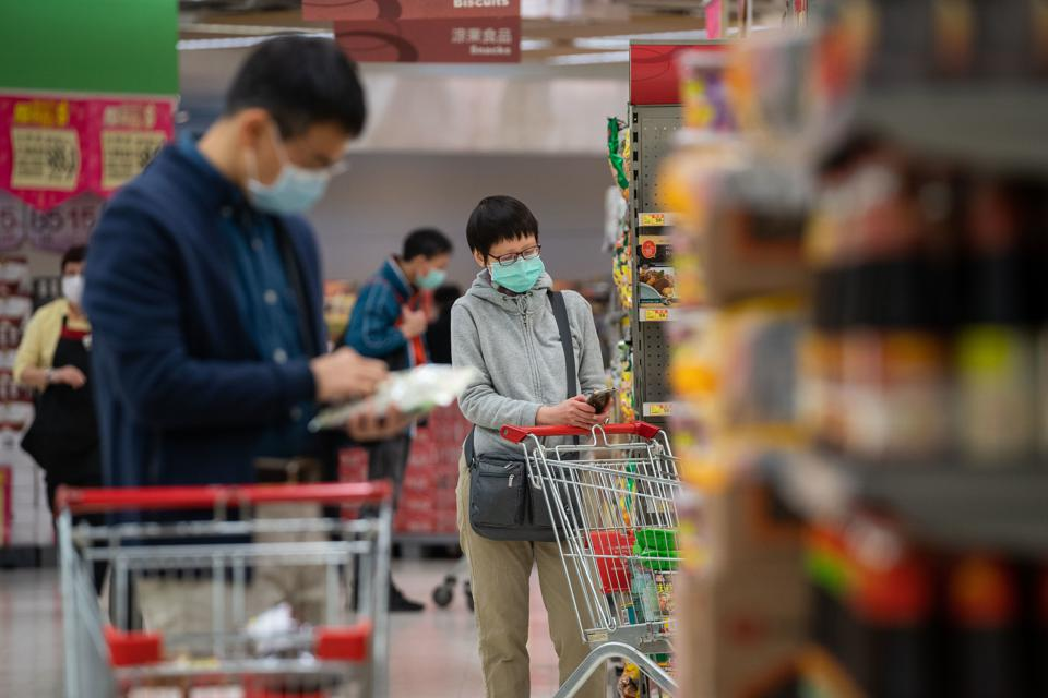 Shoppers wearing surgical masks while shopping in a...