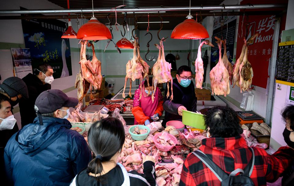 People wearing protective face masks shop at a chicken stall at a wet market in Shanghai on February 13, 2020.