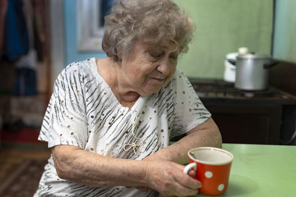 Sad elderly woman with a cup of coffee in the kitchen at home