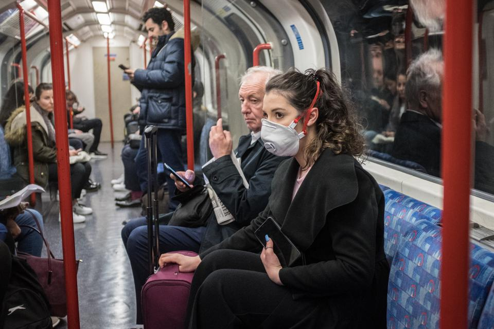 A woman seen on a tube wearing a face mask.  A total of nine...