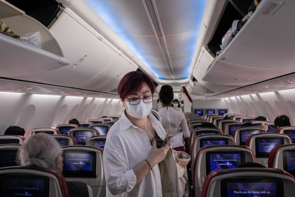 A passenger wears surgical mask inside an airplane at the...