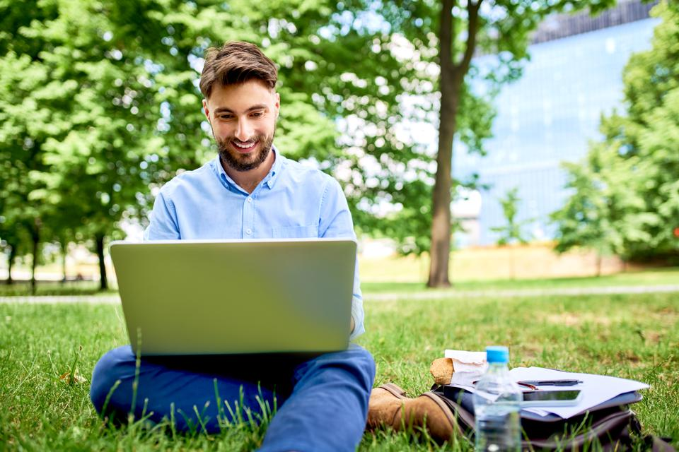 Picture of smiling young businessman working on laptop while having luch in the park