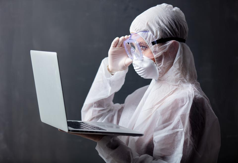 Woman in coronavirus infection outfit using a laptop