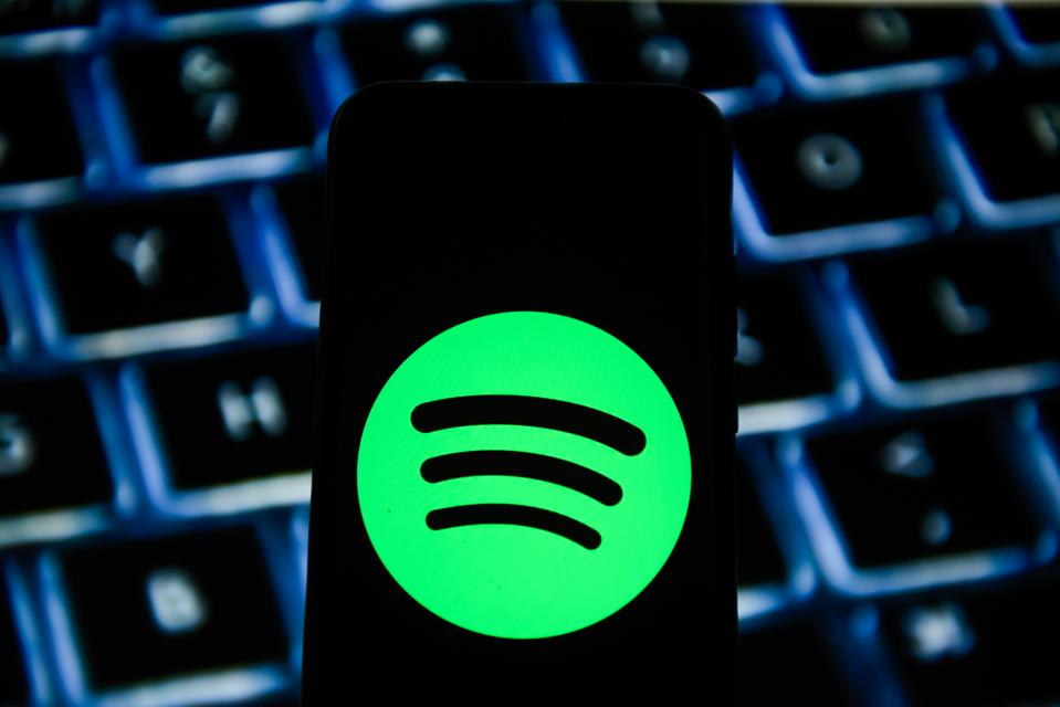 In this photo illustration a Spotify logo seen displayed on...