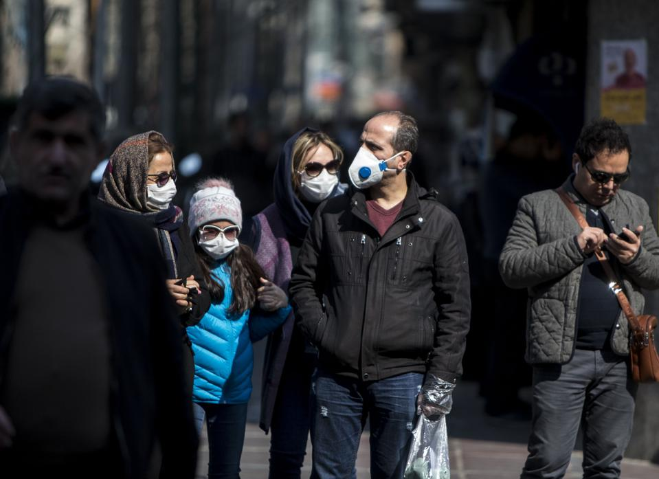People wearing masks walk in downtown Tehran, Iran