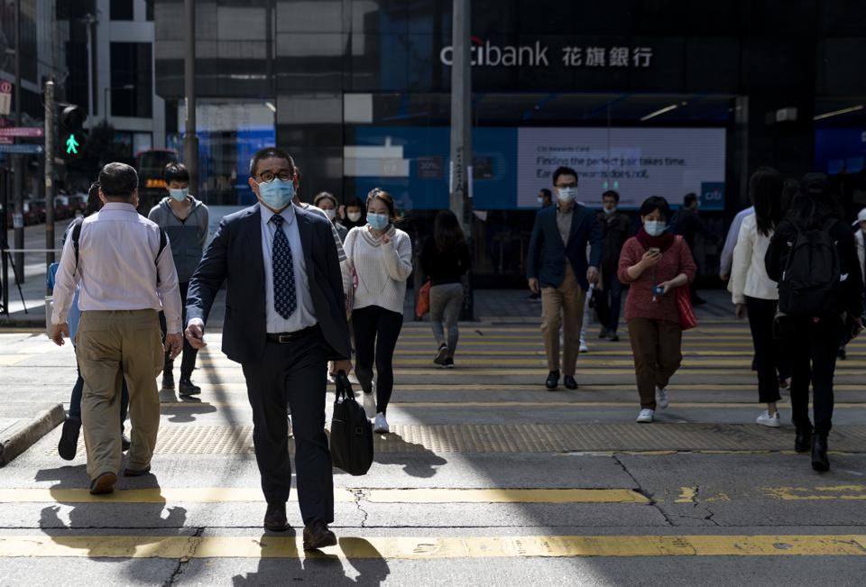 A business man wearing a face mask crosses the road in...