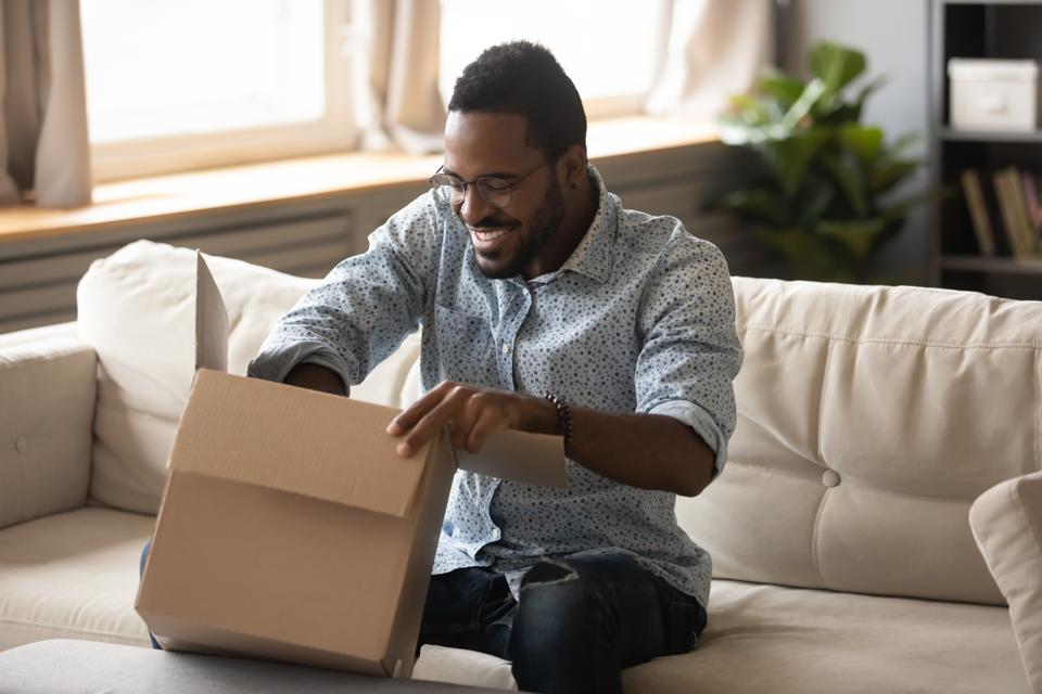 Smiling african man customer opening cardboard box parcel on sofa