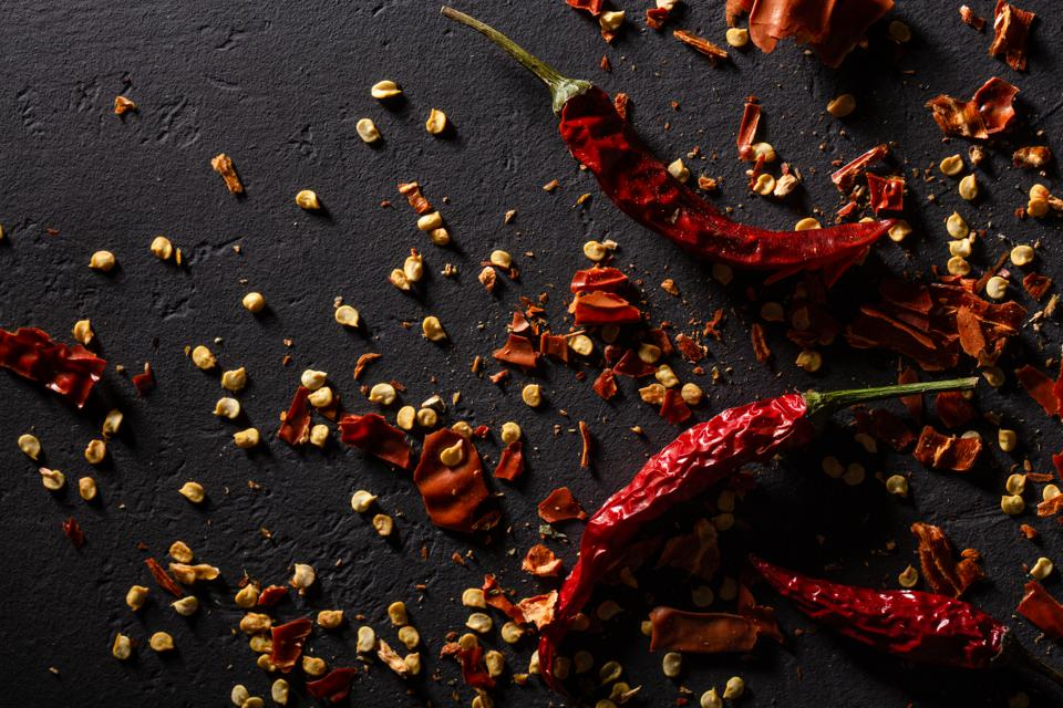 Pods of fresh red pepper on black stone. Flat lay.