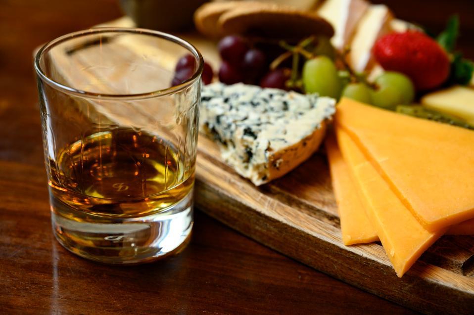 Proeverij van originele Schotse kaas en whisky, bord met Schotse kazen en verschillende soorten Schotse whisky in glazen