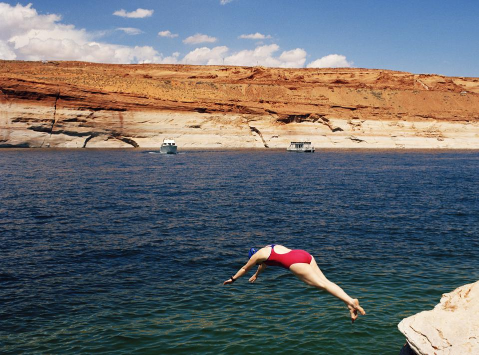 Female swimmer diving in a lake