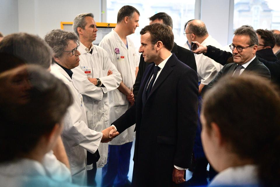 French President Emmanuel Macron shakes hands with neurologist François Salachas as he visits the Pitie-Salpetriere hospital in Paris on February 27, 2020 where the first French victim of COVID-19 passed away the day before.