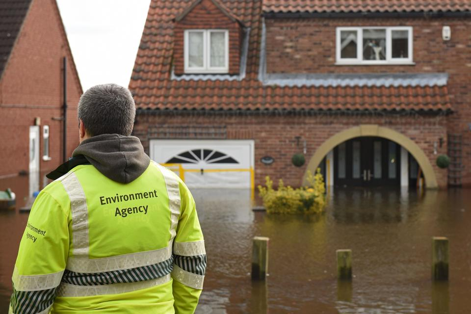 Environment Agency staff observe rising floodwater in East Cowick, northern England.