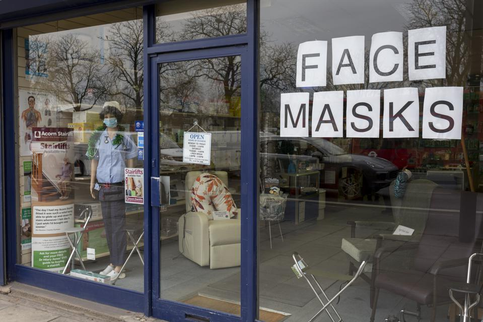 A shop window in Britain advertising face masks, with a mannequin in a nurse's outfit.