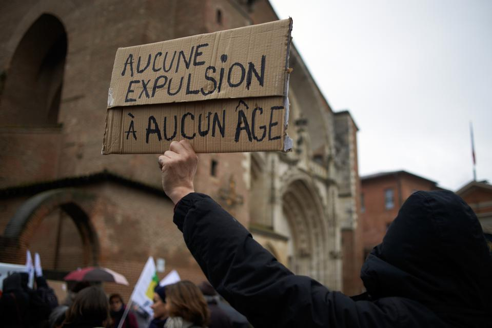 A man holds a placard reading 'No expulsion whatever the age'. A demonstration in Toulouse, France, 4 March 2020 against evictions of children and their families.