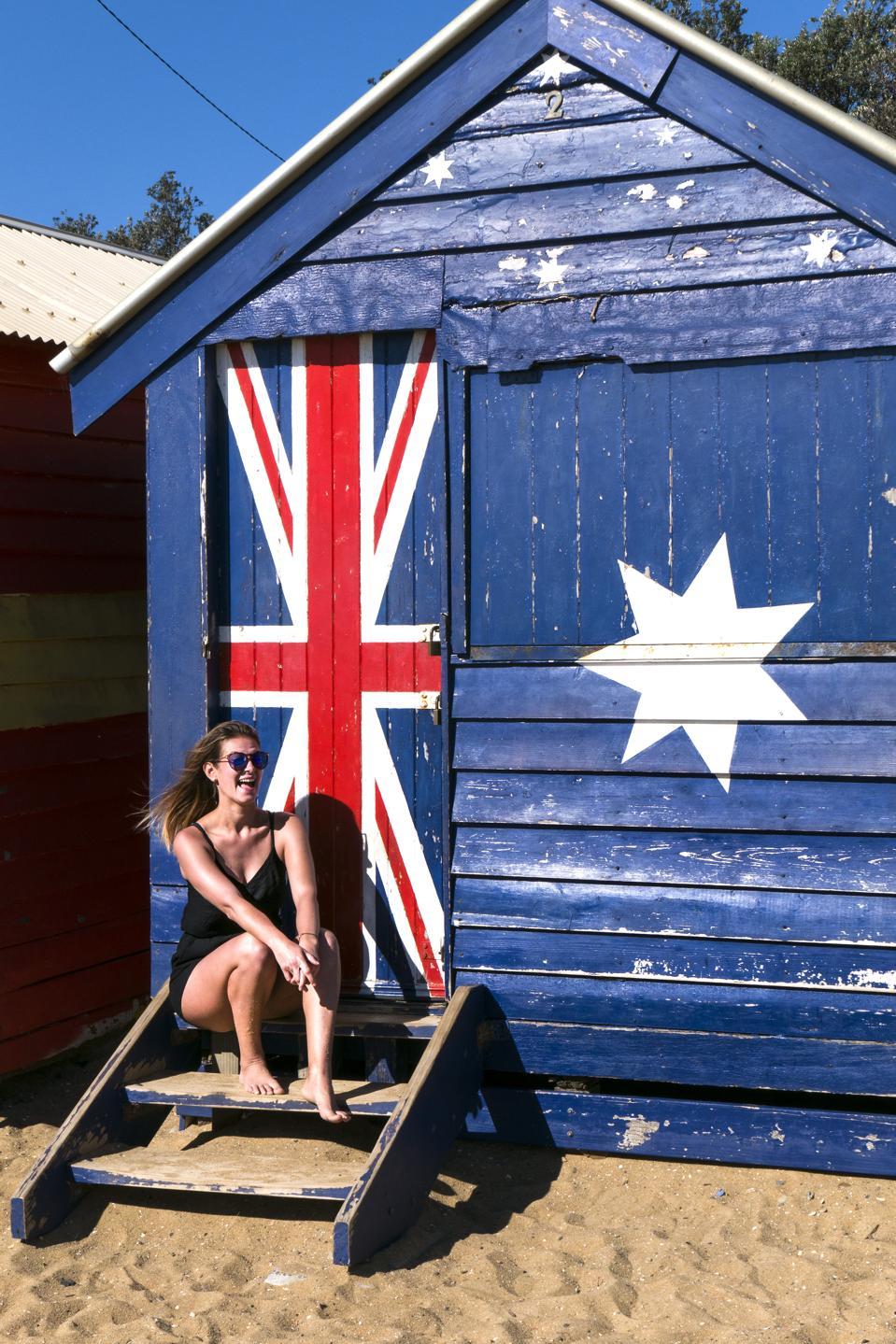 Young woman poses for photo bathing box Brighton Melbourne Australia