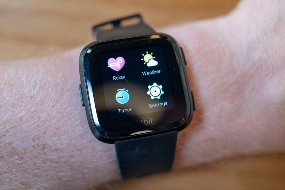 Fitbit Versa smart watch showing app menu on wrist of a man.