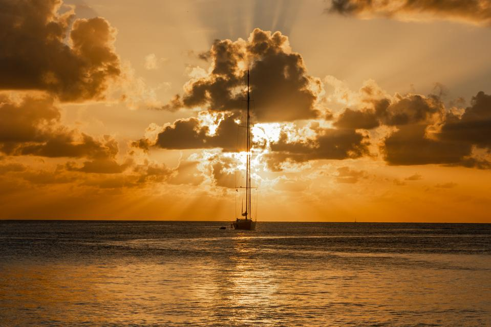 Sunset view of yacht anchored in the lagoon, Britannia bay, Mustique island, Saint Vincent and the Grenadines, Caribbean sea