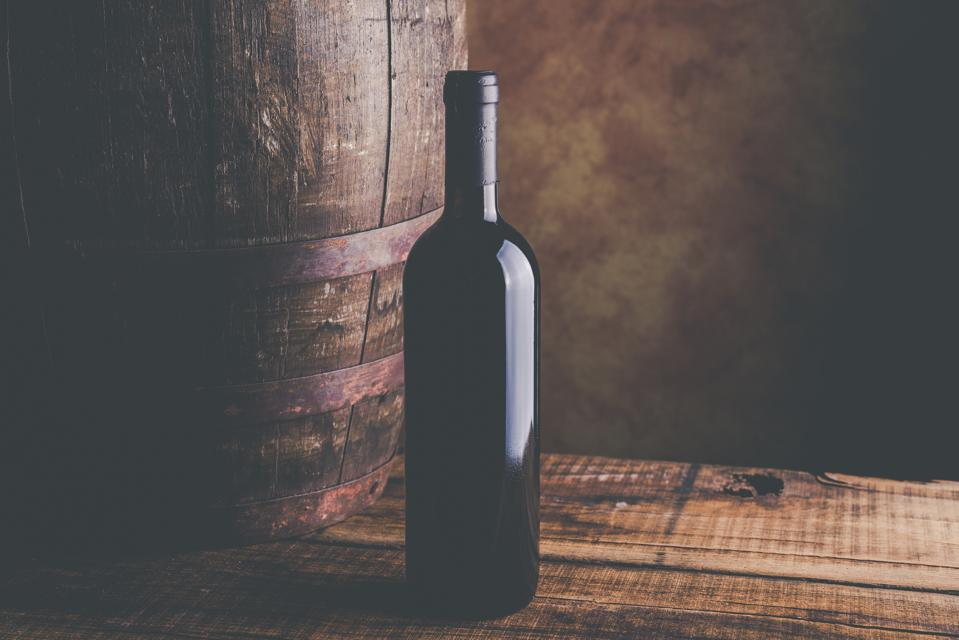 Close-Up Of Red Wine Bottle Amd Barrel On Table Against Wall