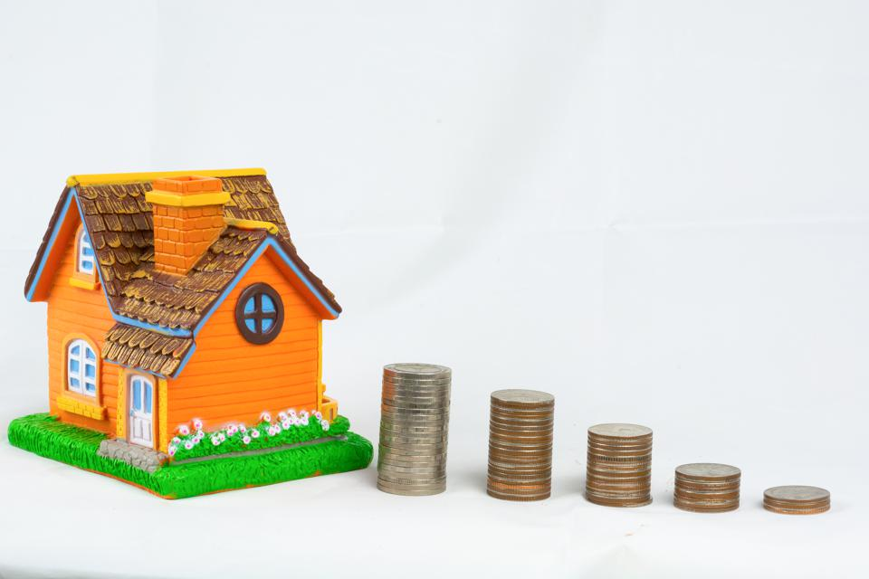 Mini house model and stack of coins. Saving money for get property concept.