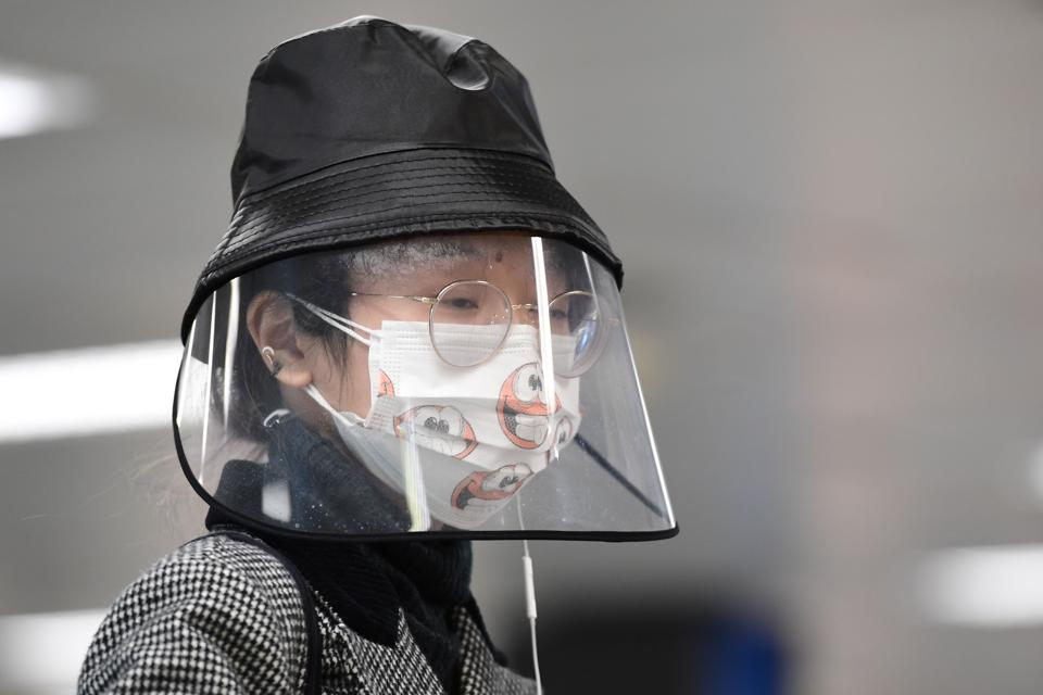 Passenger wearing Covid-19 protective face masks and face shield prepares to board flight