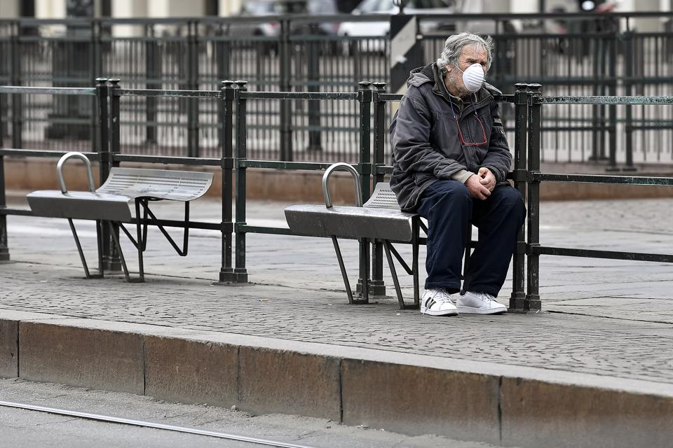 A man wearing a respiratory mask waits at bus stop. The...