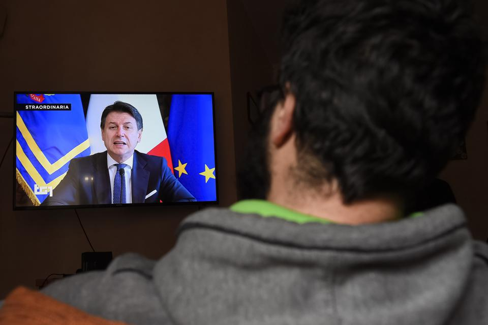 A man watches Italian Prime Minister Giuseppe Conte on TV...