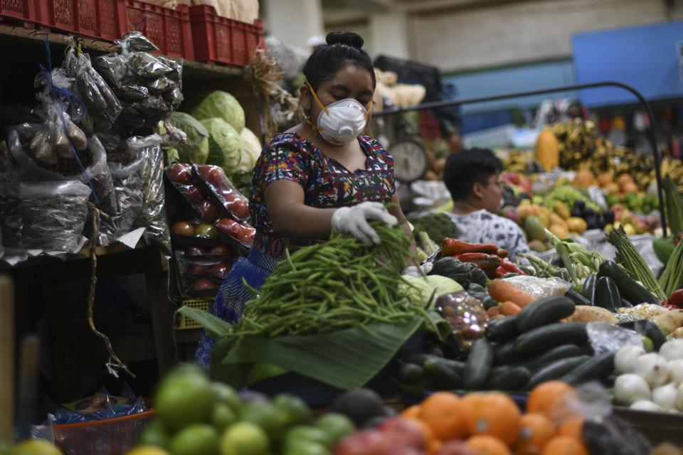 Woman with mask and gloves surrounded by heaped vegetables