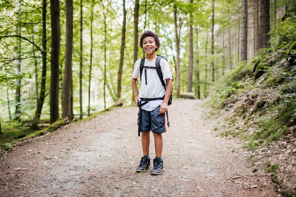 Portrait Of Young Boy Smiling While Hiking