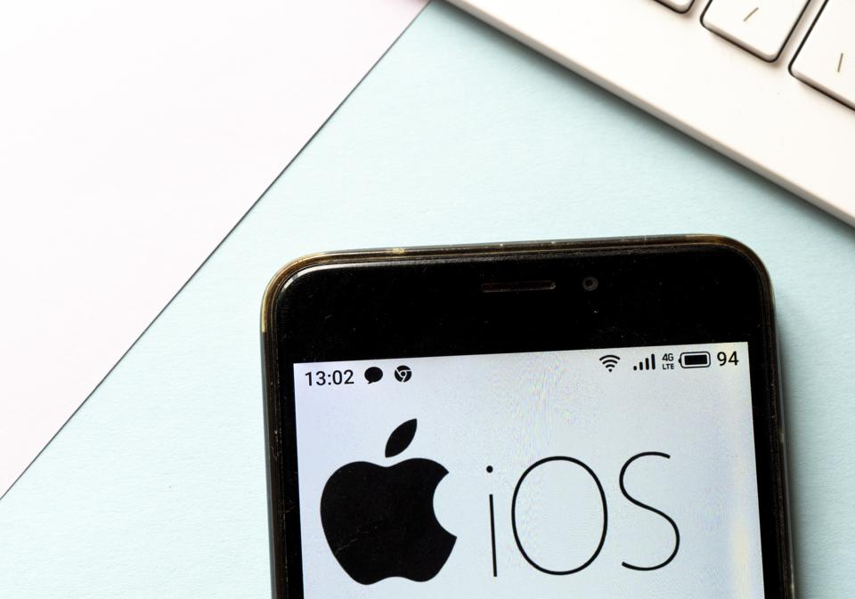 In this photo illustration an iOS logo is seen displayed on an iPhone