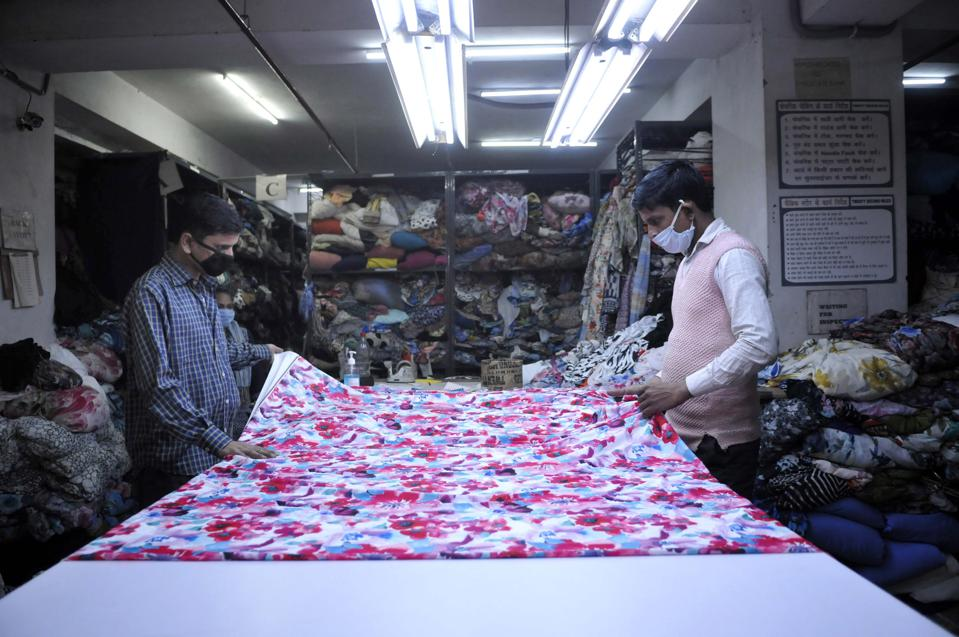 Two garment workers with masks examine a piece of floral patterned fabric
