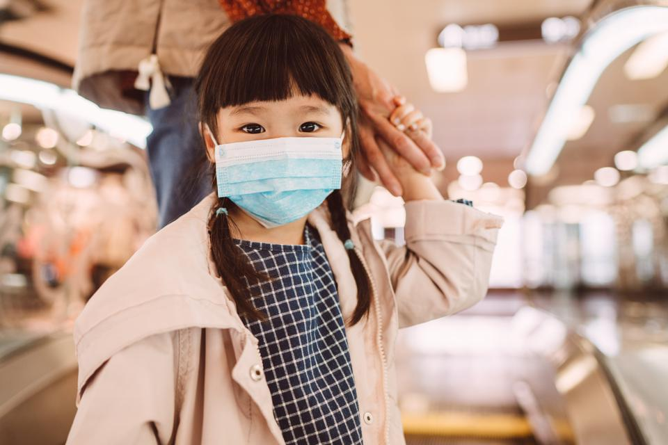 Little girl with medical face mask standing on escalator with mom