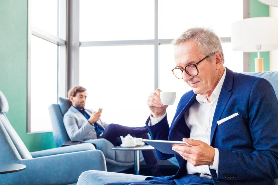 Senior businessman waiting for flight in the aiport vip lounge