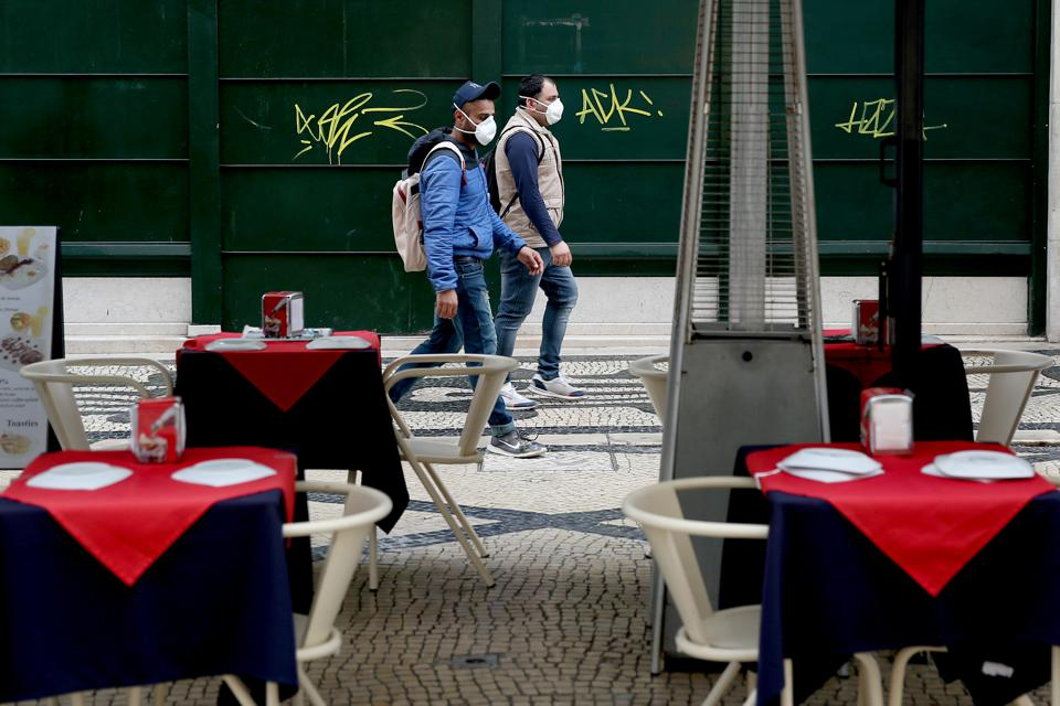 People wearing masks walk by an empty restaurant in downtown Lisbon, Portugal, on March 17, 2020. With 448 cases of infection already registered and one confirmed death, the country is feeling the impact of the COVID-19 Coronavirus pandemic.  (Photo by Pedro Fiúza/NurPhoto via Getty Images)