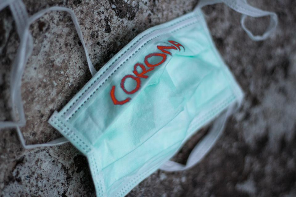 Surgical mask with the word 'corona' written on it in red