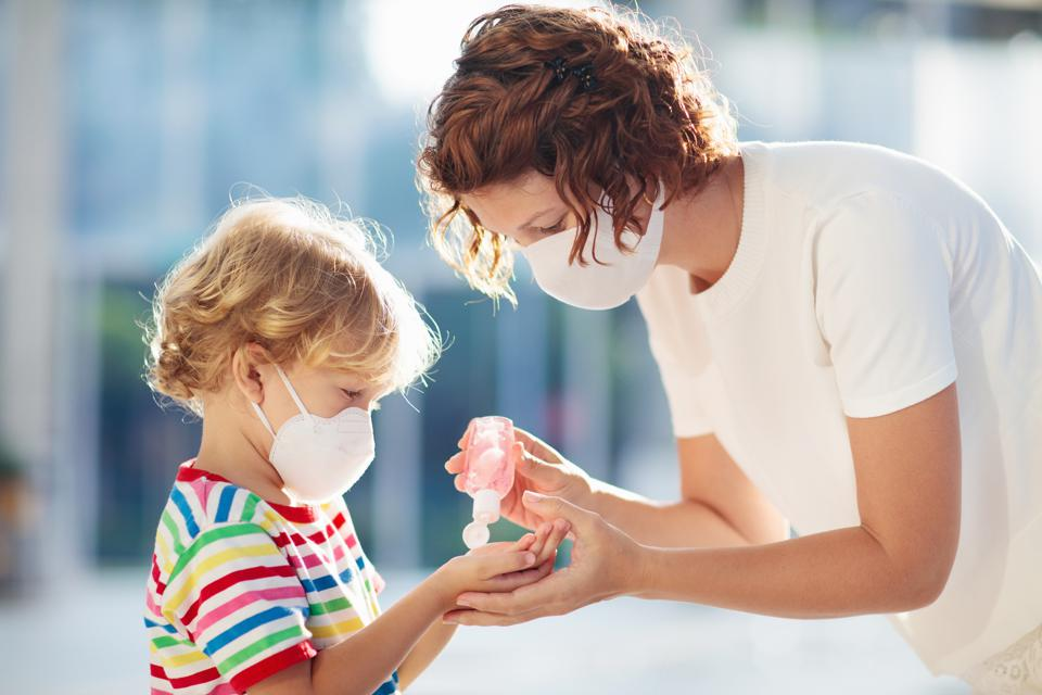 Mother and child with face mask and hand sanitizer