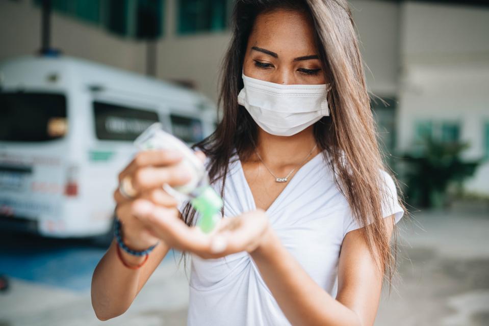 Asian women wear masks use antiseptic gel