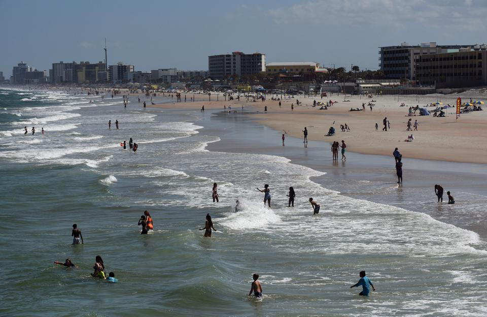 People enjoy the sun and surf during a spring break at...