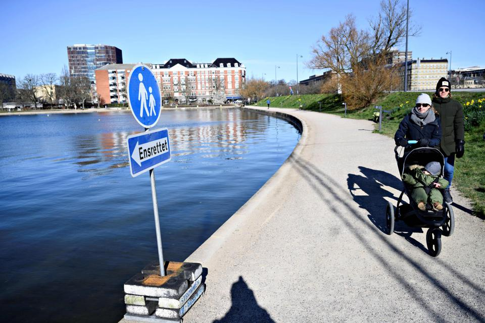 An elderly couple passes a one-way sign around lakes in Copenhagen, Denmark.