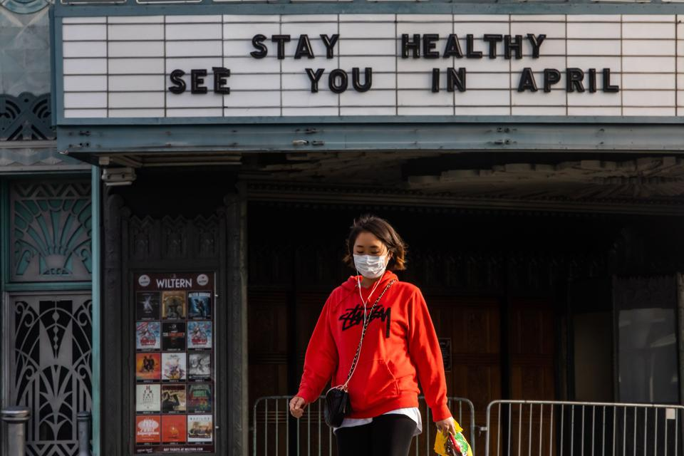 US-HEALTH-VIRUS A woman wearing a mask, walking by a closed theater in Koreatown, Los Angeles.